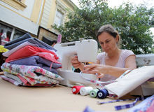 Woman sewing Stock Images