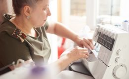 Woman in sewing studio: sewing with serger, overlocker. Fashion designers atelier. Close up side view of sewing process. Clothier sitting at her workplace and stock photography