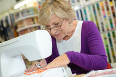 Woman sewing using sewing machine Royalty Free Stock Photography