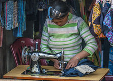 Woman sewing in the window of her shop. Royalty Free Stock Photos