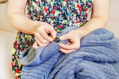 Woman sews button on cardigan. In room Royalty Free Stock Images