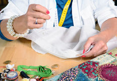 A woman sews a button. On a shirt Royalty Free Stock Image