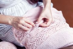 Woman sews a button. A young woman in a striped dress sews a button with a needle on a pink knitted sweater Stock Photography