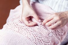 Woman sews a button. A young woman in a striped dress sews a button with a needle on a pink knitted sweater Royalty Free Stock Photo