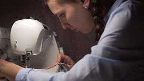A woman sews clothes on a sewing machine by the light of a lamp. Fashion, creation and tailoring. Close-up of a young woman sewing on a sewing machine. A woman stock video