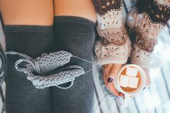Woman sews and coffee. The girl sews and holds coffee with marsmallows stock image