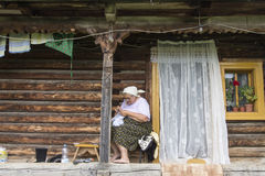 A woman sews on the patio. A woman sews seated on the patio of her typical wooden house in the Maramures region of Romania Royalty Free Stock Images