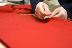 A woman sews on a red dense fabric. A woman sews on a red dense fabric with a needle Royalty Free Stock Photo