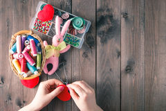 Woman sews red heart shaped toy by needle Stock Images