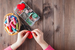 Woman sews red heart shaped toy by needle Stock Image