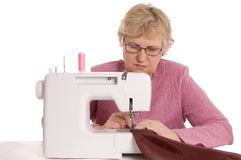 Woman sews on the sewing machine. Elderly woman sews on the sewing machine Royalty Free Stock Photo