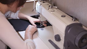 Woman sews on the sewing machine stock video