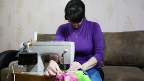 Woman sews on the sewing machine stock video footage
