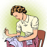Woman sews shirt thread housewife housework Stock Photo