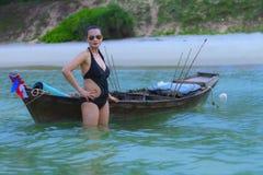 Woman sexy black bikini with small boat on beach. At Ban Krut Beach, Prachuap Khirikhan Province Thailand Stock Images