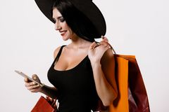 A woman in a sexy black dress and a black hat poses with a smartphone and packages Royalty Free Stock Images