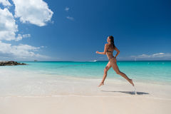 Woman with sexy body in swimsuit running on sea beach. With white sand, turquoise water and blue sky on sunny day on natural environment. Sun tanning, bathing Stock Photo