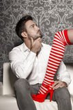 Woman in sexy christmas outfit trying seduce man on sofa Stock Image