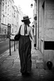 Woman with sexy dress and hat walking in the street Royalty Free Stock Images