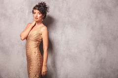 Woman in sexy dress pose standing while touching her neck Royalty Free Stock Photos