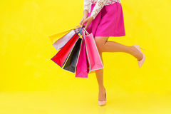 Woman with sexy legs holding shopping bags Stock Image