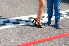 Woman sexy legs and motorsport driver on asphalt track Royalty Free Stock Images