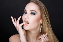 Woman sexy lips. Young beautiful woman girl lady bites his finger, touch lips. model fashionable hairdo professional makeup trendy green shadows smoky eyes Royalty Free Stock Photography