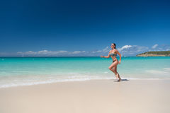 Woman in sexy swimsuit running on beach. With white sand, turquoise sea or ocean and blue sky on sunny day on natural environment. Sun tanning, bathing. Summer Stock Photography