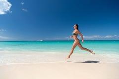 Woman in sexy swimsuit running on sea beach Stock Photo