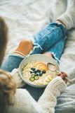 Woman in shabby jeans and sweater eating vegan breakfast Royalty Free Stock Photos