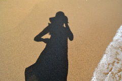 Woman shadow on the beach sand Stock Image