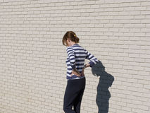 Woman with shadow on brick wall Stock Images