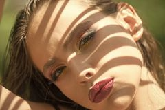 Woman with shadow on face on sunny day, look. Woman with fashion makeup, eyes and lips visage. Beauty model with makeup Royalty Free Stock Photos