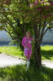 The woman in a shadow of the tree blossoming in the pink flowers Stock Images