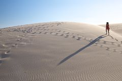 Woman and shadow up the dune Royalty Free Stock Photo