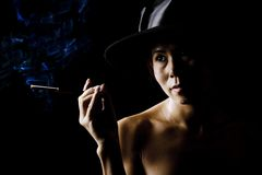 Woman in shadow wearing a black hat with cigarette Royalty Free Stock Photo