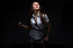 Woman in shadow with whip looking up Royalty Free Stock Image