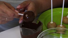 A woman shakes cake pops in dark chocolate. For even distribution of chocolate on the ball. Next on the table are blanks for cake. Pops stock video footage