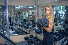 Woman shakes her biceps at gym Royalty Free Stock Images