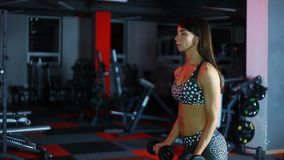 The woman shakes her muscles. Girl with athletic body lifts dumbbells, shakes her shoulders in the gym stock video