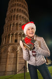 Woman shaking Christmas gift box near Leaning Tower of Pisa Royalty Free Stock Image