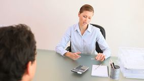 Woman shaking hand to a businessman. While sitting at a desk stock footage