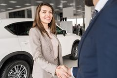 Woman Shaking Hands with Car Salesman. Portrait of happy young women shaking hands with car salesman after buying new luxury car in dealership showroom Stock Photos