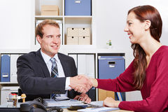 Woman shaking hands with consultant. Smiling women shaking hands with financial consultant in the office Stock Images