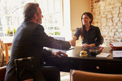 Woman shaking hands with guest at check-in desk of a hotel Stock Photography