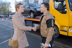 Woman shaking hands with man who has recovered car Stock Photos