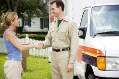 Woman shaking hands with removal man beside his van Royalty Free Stock Image