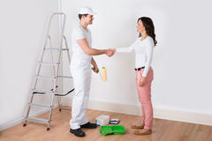 Woman Shaking Hands To Painter With Paint Roller At Home Royalty Free Stock Photo