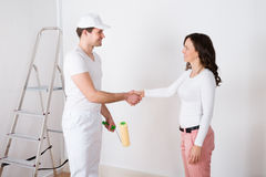 Woman Shaking Hands To Painter With Paint Roller At Home Stock Photos