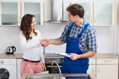 Woman Shaking Hands To Plumber Royalty Free Stock Photos